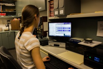 Former archives assistant Anna Bush digitizes an archival tape in the Conservatory's library.
